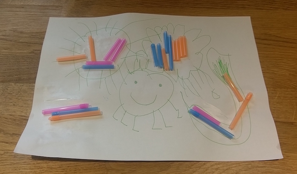A child's drawing made with straws.